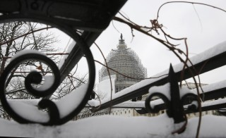 The U.S. Capitol building is seen through a snow covered trellis at the start of the 114th Congress on the Capitol grounds in Washington. Photo by Jim Bourg/Reuters
