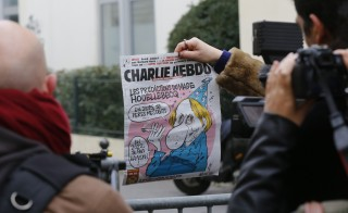 A member of the media makes images of the front page of Charlie Hebdo which shows a caricature of French author Michel Houellebecq near the Paris offices of Charlie Hebdo, a satirical newspaper, after a shooting January 7, 2015. Twelve people including two police officers were killed in a shooting at the Paris offices of the satirical weekly Charlie Hebdo on Wednesday, a police spokesman said in an update on the death toll. The French president described the shooting as without doubt a terrorist attack. Photo by Jacky Naegelen/Reuters