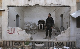 A rebel fighter stands inside a damaged room near the frontline against forces loyal to Syria's President Bashar al-Assad in Aleppo Jan. 8, 2015. Photo by Jalal Al-Mamo/Reuters