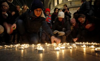 A woman in front of the French cultural center in Belgrade places a lit candle as a tribute to victims of a shooting by gunmen at the offices of French satirical weekly Charlie Hebdo. Photo by Djordje Kojadinovic/Reuters