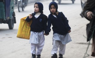 Girls carry their school bags as they walk along a road while heading to their school after it reopened in Peshawar January 12, 2015. Photo by Khuram Parvez/Reuters