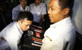Officials carry a box containing the flight data recorder from AirAsia Flight QZ8501 at the National Transportation Safety Committee office in Jakarta January 12, 2015. Indonesian navy divers retrieved the black box flight data recorder from the wreck of the AirAsia passenger jet on Monday, a major step towards unravelling the cause of the crash that killed all 162 people on board. Photo by Beawiharta/Reuters
