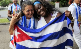 Recently released dissidents Aide Gallardo (L) and Sonia Garro hold the Cuban national flag during a march in Havana January 11, 2015. Cuba has released all 53 prisoners it had promised to free, senior U.S. officials said. Photo by Stringer/Reuters