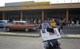 A passenger pushes a luggage cart after arriving on a charter flight from Tampa, Florida, at the airport in Havana January 15, 2015. The United States rolled out a sweeping set of measures on Thursday to significantly ease sanctions on Cuba, opening up the country to expanded U.S. travel, trade and financial activities. The 54-year-old U.S. embargo on Cuba will remain in place - only Congress can lift it. Photo by Stringer/Reuters
