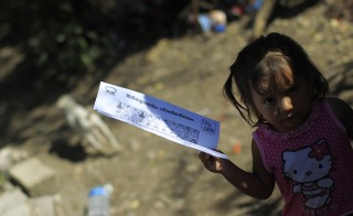 A child holds a flyer with the faces of the 43 missing students from the Ayotzinapa Teacher Training College, during the search of the students in Lomas del Zapatero, on the outskirts of Iguala, Guerrero, January 15, 2015. The Attorney General's office said it had granted a request from the families to allow them to search military barracks throughout Guerrero and other parts of Mexico. REUTERS/Jorge Dan Lopez (MEXICO - Tags: CRIME LAW EDUCATION POLITICS CIVIL UNREST) - RTR4LM0P