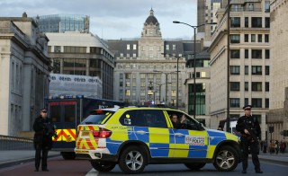 Armed police stop traffic during a vehicle search on London Bridge in London