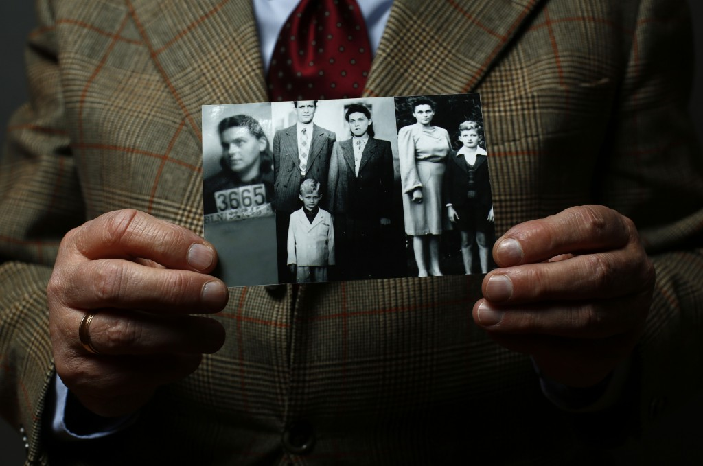Auschwitz concentration camp survivor Jacek Nadolny holds up a wartime photo of his family in Warsaw