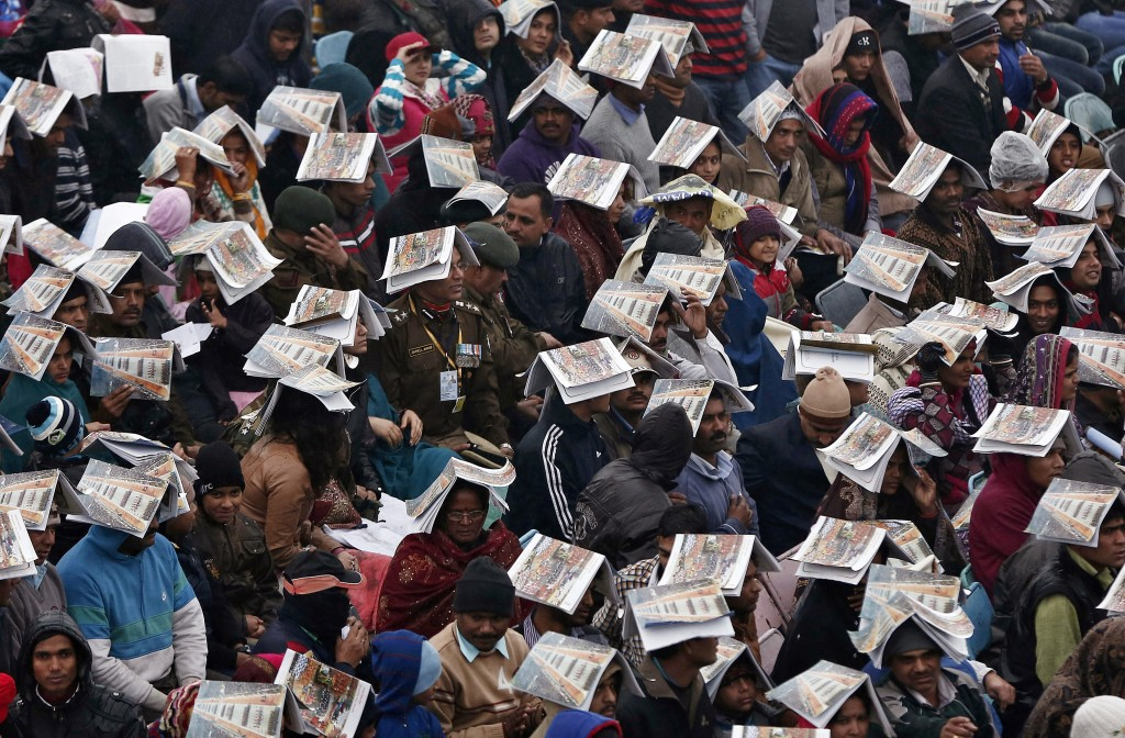 Spectators use catalogues to protect themselves from rain as they watch the Republic Day parade in New Delhi. Photo by Adnan Abidi/Reuters