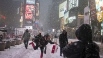 Lulu Marin, visitor from San Lorenzo, Paraguay, poses for photographs during a snow storm in Times Square, New York