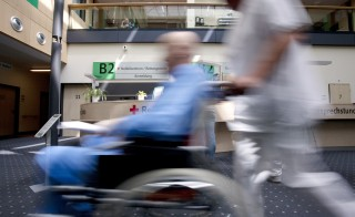 A patient is pushed in a wheelchair past the emergency check-in desk by a member of the medical staff at the Helios hospital Berlin, operated by Fresenius SE, in Berlin, Germany, on Tuesday, June 5, 2012. Rhoen Klinikum AG's management said it will back the 3.1 billion-euro ($3.9 billion) takeover offer from Fresenius SE, contingent on an agreement to maintain certain jobs and locations at the German hospital operator. Photographer: Michele Tantussi/Bloomberg