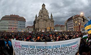 A banner reading 'Wall of friendship without borders' can be seen in the foreground as thousands of people take part in a rally in Dresden, Germany. (Credit: Getty Images)