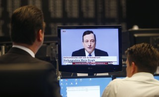 Traders watch the news conference held by European Central Bank (ECB) President Mario Draghi, during a trading session at the Frankfurt stock exchange Jan. 22, 2015. The European Central Bank agreed on Thursday to embark on a quantitative easing (QE) program. Photo by    REUTERS/Ralph Orlowski.
