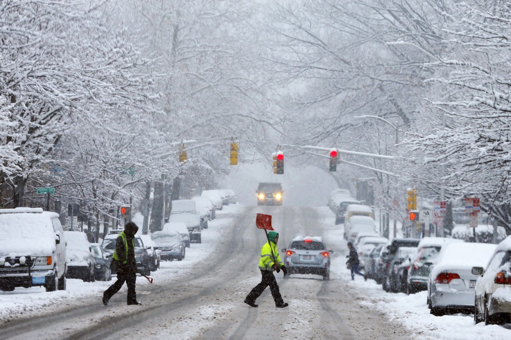 A snow shoveler crosses a street during a winter snowstorm in Cambridge, Massachusetts January 24, 2015 Blizzard warnings and watches went in effect Sunday morning for more than 29 million people in areas in the Northeast. REUTERS/Brian Snyder