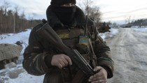 A Ukrainian serviceman stands guard at his position in the village of Luhanska, Luhansk region