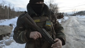 A Ukrainian serviceman stands guard at his position in the village of Luhanska, Luhansk region