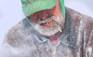 David Peppard of Eddington, Maine, is engulfed in the fine chips of ice thrown by the ice saw while working at Cobb's Pierce Pond Camps in Pierce Pond Township.  Peppard is one of the several guides who works at the camps during the fishing season and is a regular participant in the annual ice harvest. Photo by Gabor Degre/Bangor Daily News