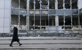 A woman walks by a building that was damaged by shelling last September, Donetsk, February 15, 2015. Photo by Baz Ratner/Reuters