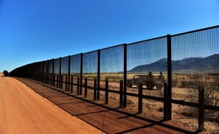 A small group from the Mexican Army can be seen through the fence that stands on the U.S./Mexico border in 2013 in Naco, Arizona. The Obama administration deported fewer immigrants over the past 12 months than at any time since 2006, the Associated Press reports. Photo by Jahi Chikwendiu/The Washington Post