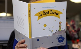 "A woman reads a new edition of ""The Little Prince"" book on April 11, 2013 in Paris. France is marking the 70th anniversary of the world-loved ""The Little Prince"" with a host of special editions, including a new biography of its author, native son Antoine de Saint-Exupery. ""Le Petit Prince"", a series of parables in which a boy prince recounts his adventures among the stars to a downed pilot on Earth, was first published in New York in 1943, in English and French.   AFP PHOTO / PATRICK KOVARIK        (Photo credit should read PATRICK KOVARIK/AFP/Getty Images)"