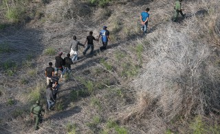 U.S. Border Patrol agents escort a group of undocumented immigrants into custody near the U.S/ Mexico border in Texas. Photo by John Moore and Getty Images