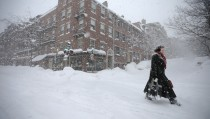 A woman walks through the snow down Charles Street during a winter blizzard in Boston