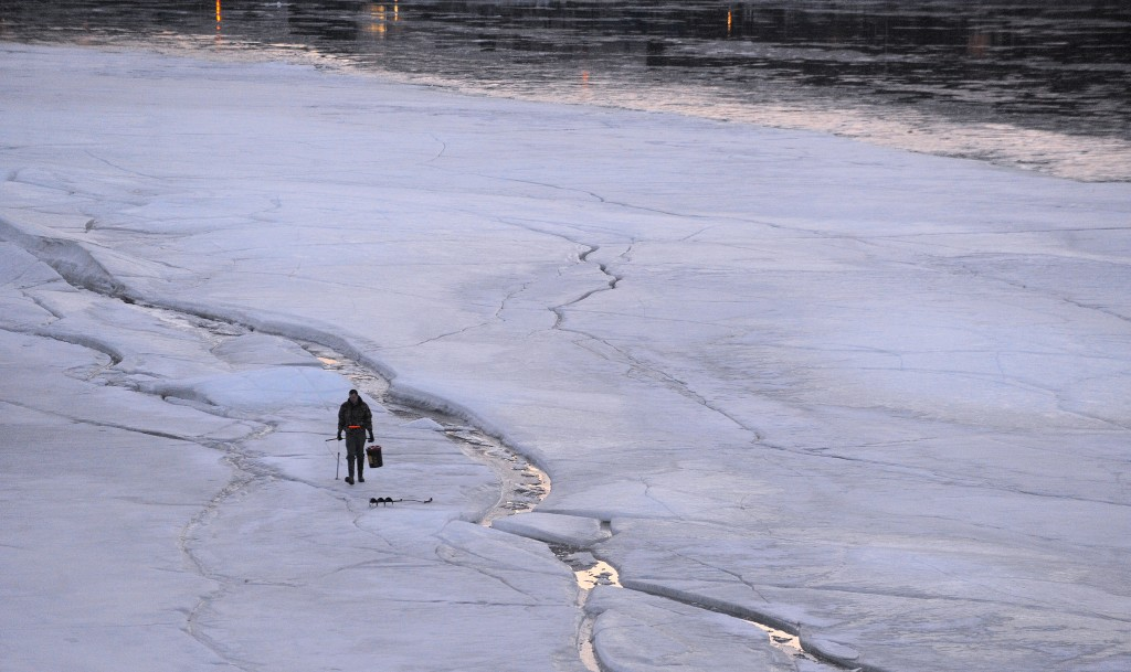 A man tries his luck catching smelts through a crack in the ice of the Penobscot River about 25-30 yards from the Brewer shore Saturday afternoon.  The man didn't want to be identified, but he said he didn't catch anything. He measured the ice where he was fishing and it was 16 inches thick. Photo by Gabor Degre/Bangor Daily News