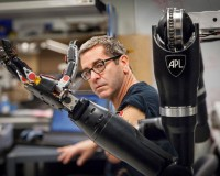 Miles O'Brien operating the modular prosthetic limb at the Johns Hopkins Applied physics laboratory.  Funded by the Pentagon research enterprise DARPA, it is the most sophisticated prosthetic limb in the world. Photo by the Applied Physics Laboratory