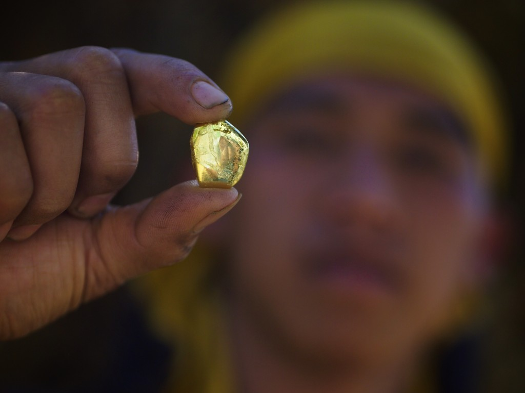 A miner holds a gold nugget, extracted from ore at an illegal gold mine in the Philippines. Photo by Larry C. Price.