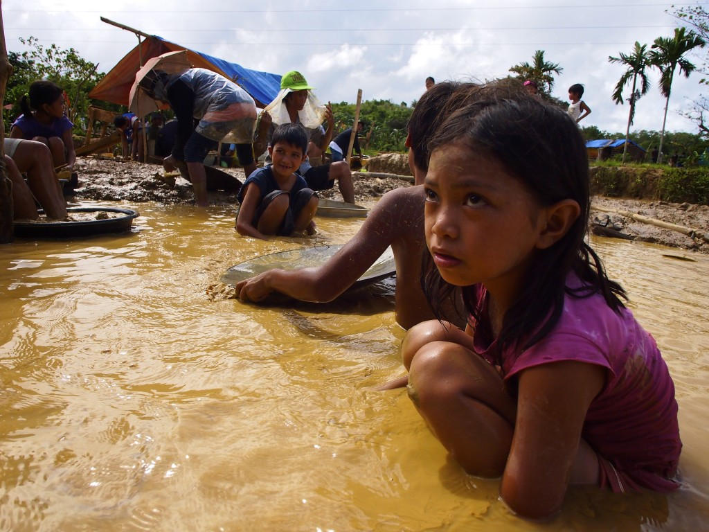Children pan a muddy slice that will eventually be mixed with toxic mercury or other chemicals to extract gold. Photo by Larry C. Price