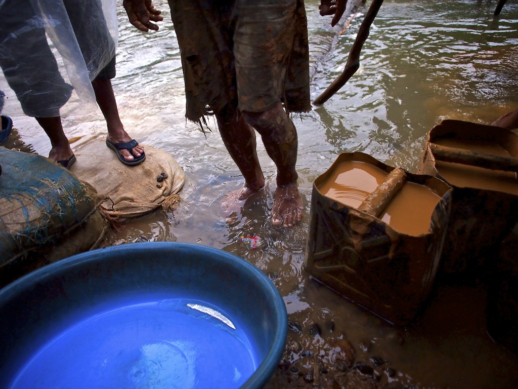 "Young boys process gold using plastic tubs and mercury along the banks of the Guinobatan River outside the town of Aroroy.  A liquid sludge, made by tumbling gold ore and water in mechanized tumblers, is mixed with mercury then  ""panned."" Mercury is often spilled into the river creating an environmental hazard.  Photo by Larry C. Price"