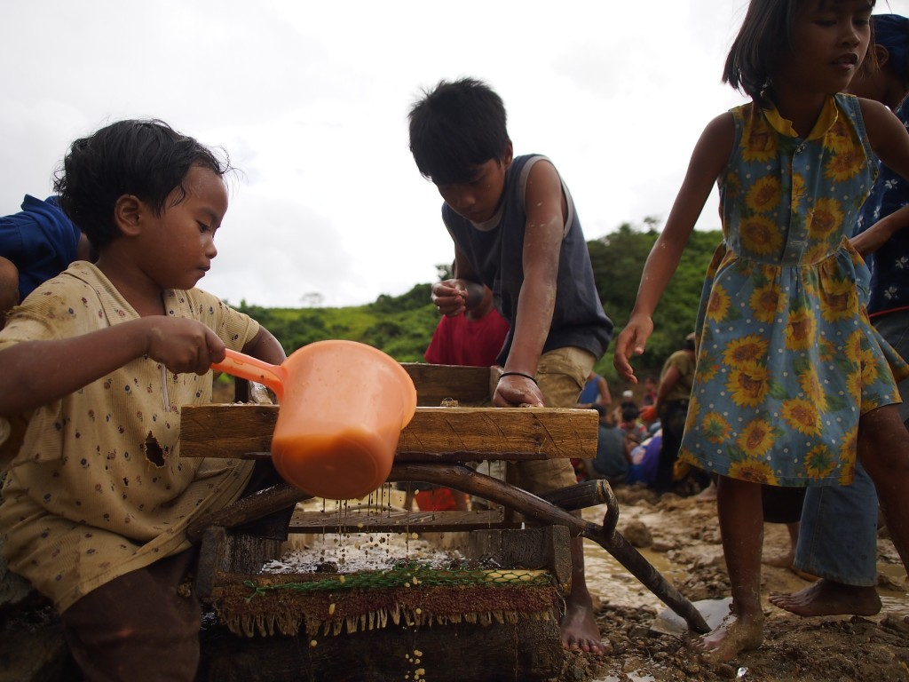 Children sift through ore at an illegal gold mine in the Philippines. Photo by Larry C. Price