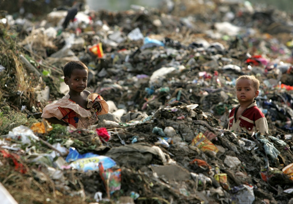 Children of rag-pickers stand amid a heap of garbage on the outskirts of New Delhi in 2006. Photo by Kamal Kishore/Reuters