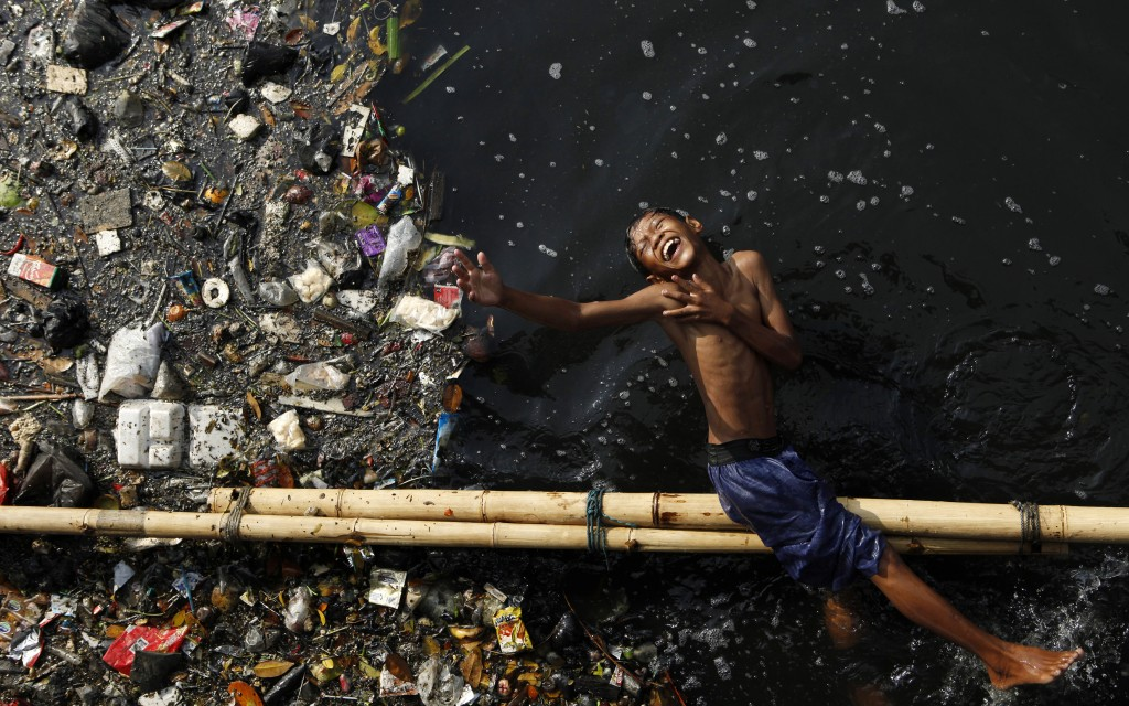 A boy plays in a polluted river after school at Pluit dam in Jakarta, Indonesia, June 5, 2009. Photo by Beawiharta/Reuters