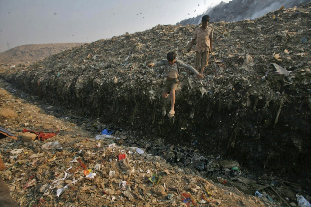 Waste collector Dinesh Mukherjee, 11, watches his friend jump over a puddle of toxic liquid at the Ghazipur landfill in New Delhi November 10, 2011. Photo by Parivartan Sharma/Reuters