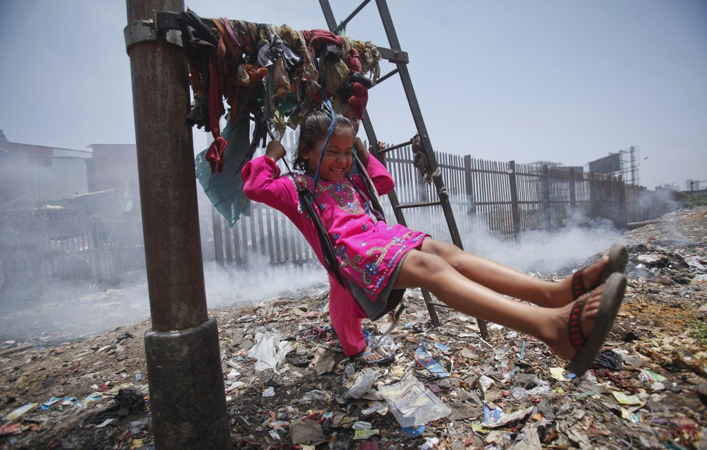 Sana, a five-year-old girl, plays on a cloth sling hanging from a signalling pole as smoke from a garbage dump rises next to a railway track in Mumbai in 2012. Photo by Vivek Prakash/Reuters