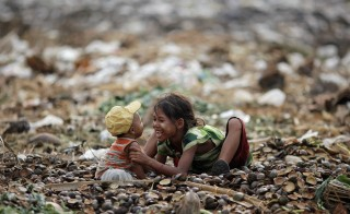 A girl plays with her brother as they search for usable items at junkyard near the Danyingone station in Yangon's suburbs in Myanmar in 2012. Photo by Damir Sagolj/Reuters