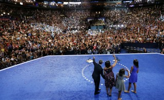 U.S. President Barack Obama (L) waves at supporters as he leads his family - wife Michelle (2nd L), and daughters Sasha and Malia (R) across the stage at the Democratic National Convention in Charlotte, North Carolina on Sept. 6, 2012. Photo by Rick Wilking/Reuters