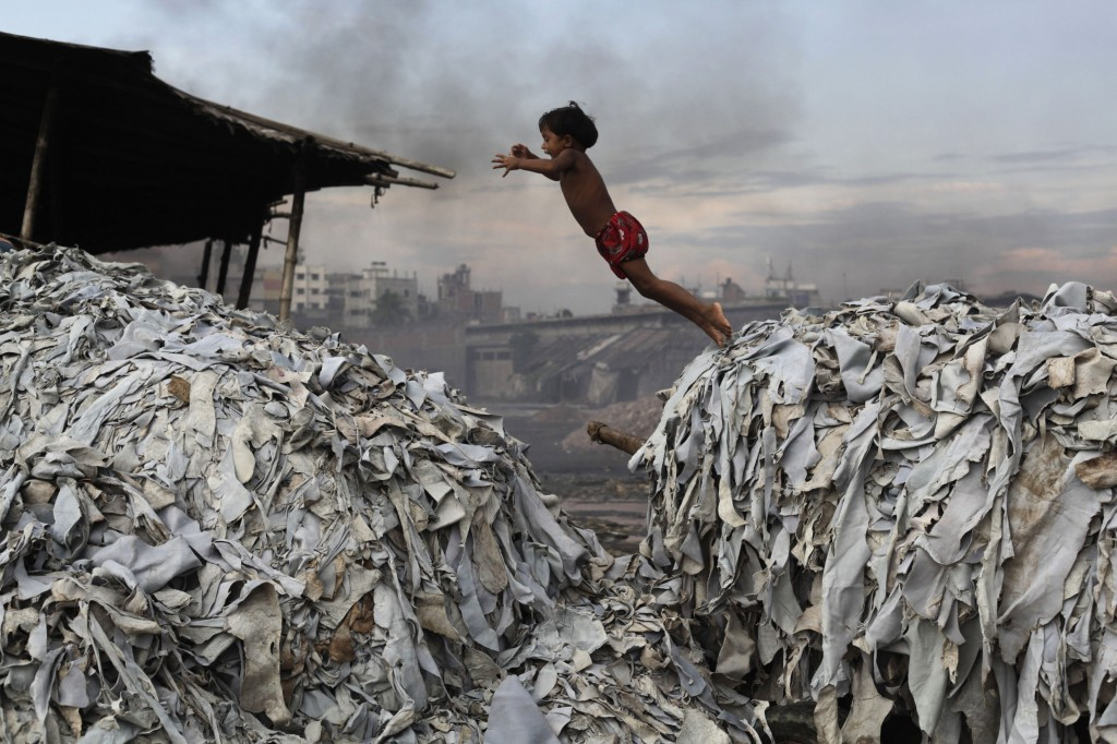 A child jumps on the waste products that are used to make poultry feed as she plays in a tannery at Hazaribagh in Dhaka in 2012. Luxury leather goods sold across the world are produced in a slum area of Bangladesh's capital where workers, including children, are exposed to hazardous chemicals and often injured in horrific accidents. Photo by Andrew Biraj/Reuters