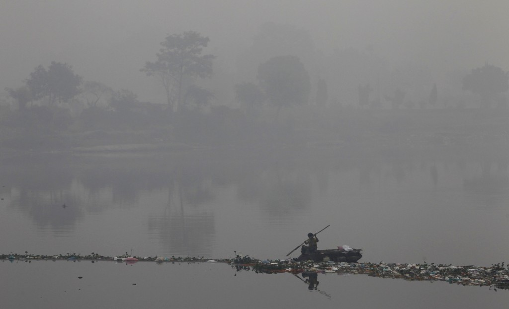 A rag picker collects recyclable materials in the polluted waters of river Yamuna amid dense smog in the old quarters of Delhi November 8, 2012. Indians are at high risk of respiratory ailments, heart disease and lung cancer, according to World Health Organization (WHO) data that showed Delhi's air had almost 10 times the recommended level of PM10 particulate matter, or particles small enough to penetrate to the deepest part of the lungs and cause health problems. REUTERS/Mansi Thapliyal (INDIA - Tags: ENVIRONMENT SOCIETY HEALTH TPX IMAGES OF THE DAY) - RTR3A5J3
