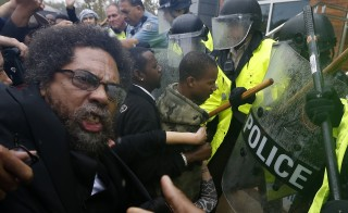 Activist Cornel West is knocked over during a scuffle with police during a protest at the Ferguson Police Department in Ferguson, Missouri on Oct. 13, 2014. Photo by Jim Young/Reuters