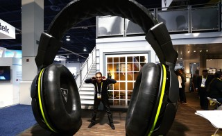 International Consumer Electronics show attendee Nezar Khajah poses with a giant pair of headphones, Las Vegas, Nevada January 6, 2015. On Friday, the World Health Organization said more than 1 billion of the world's young people are at risk of hearing loss. Photo by Rick Wilking/Reuters