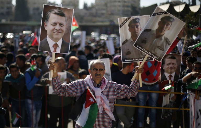 Protesters hold up pictures of Jordanian King Abdullah and pilot Muath al-Kasaesbeh, as they chant slogans during a rally in Amman to show their loyalty to the King and against the Islamic State, Feb. 5, 2015. Photo by Muhammad Hamed/Reuters