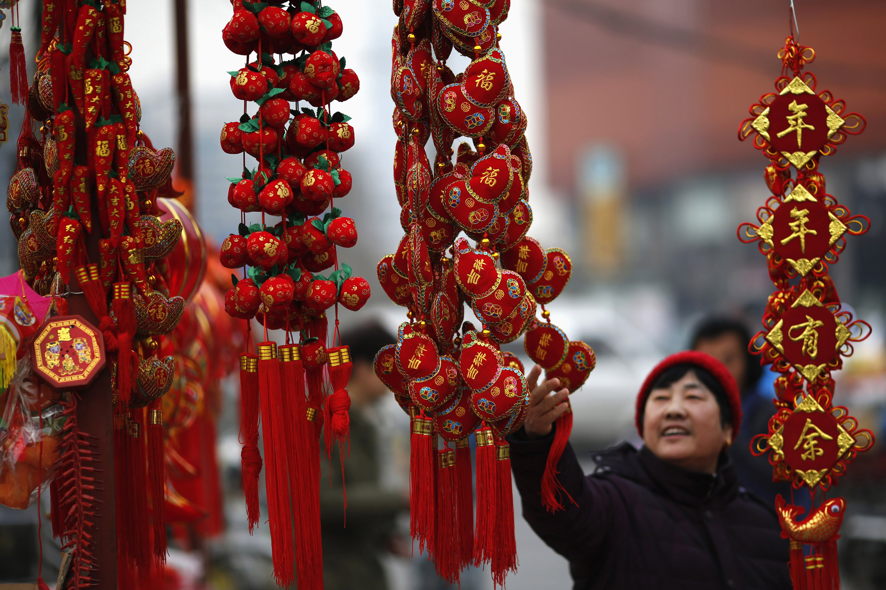 A woman looks at traditional decorations celebrating for the upcoming Chinese Lunar New Year at a market in Beijing February 6, 2015. Photo by Kim Kyung-Hoon/REUTERS.
