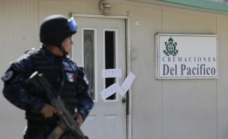 A police officer stands guard outside the sealed-off building housing a crematorium in Llano Largo, on the outskirts of the reort town of Acapulco. At least 61 bodies were discovered Thursday in the abandoned crematorium, mostly in a state of decomposition. Photo by Henry Romero/Reuters