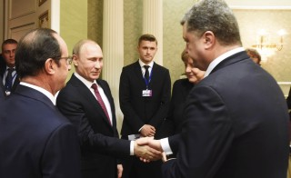 Vladimir Putin shakes hands with Petro Poroshenko, with Francois Hollande and Angela Merkel standing nearby, as they take part in peace talks on resolving the Ukrainian crisis in Minsk