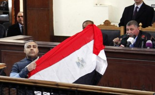 Al Jazeera journalist Mohamed Fahmy raises an Egyptian national flag while talking to the judge during his retrial at a court in Cairo Feb. 12, 2015. Photo by Asmaa Waguih/Reuters