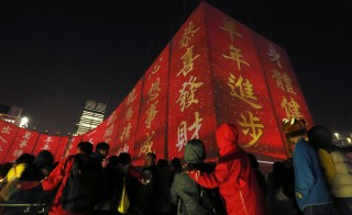 "Images of ""Fai Chun"" or Chinese New Year couplets, which read, ""Wishing you wealth and prosperity"" (3rd R) and ""Progress in Year of the Goat"" (2nd R), are shown on the facade of the Hong Kong Cultural Centre in Hong Kong February 12, 2015. The Chinese Lunar New Year on February 19 will welcome the Year of the Sheep. Photo by Bobby Yip/Reuters"