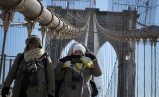 People walk during low temperatures through the Brooklyn bridge in New York
