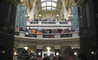 Union members, some wearing hard hats and overalls, gather inside the Wisconsin State Capitol building in Madison, Wisconsin to rally against right-to-work on February 24, 2015.