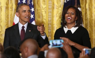 U.S. President Barack Obama gestures next to First Lady Michelle Obama at a reception celebrating African American History Month in the East Room of the White House in Washington February 26, 2015. Obama plans trip to Selma, Alabama focusing on civil rights of the past and present. Photo by Yuri Gripas/REUTERS.